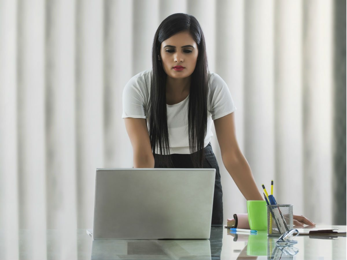 burn more calories at work, woman standing at her desk