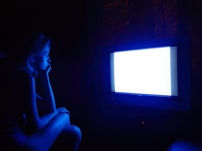 blue light damage similar to sunburn, woman watching tv late at night