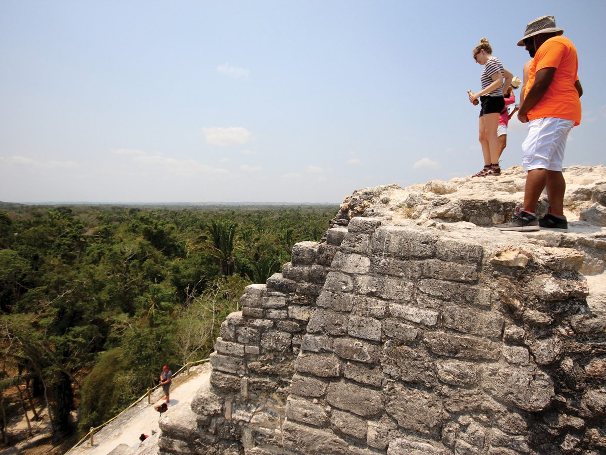 Belize Lamanai Ruins, Tourists looking over the Belize Lamani ruins