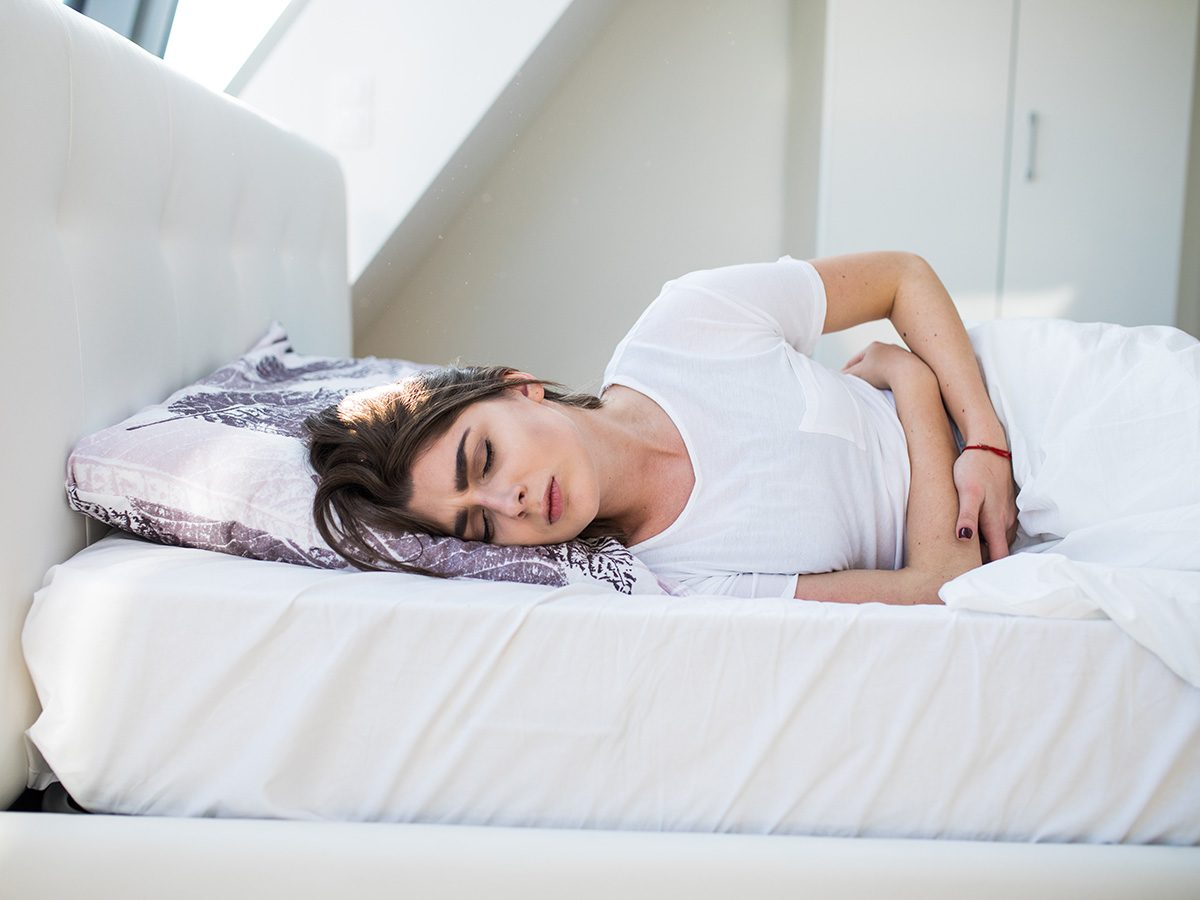 Aging, woman with period cramps lying in bed
