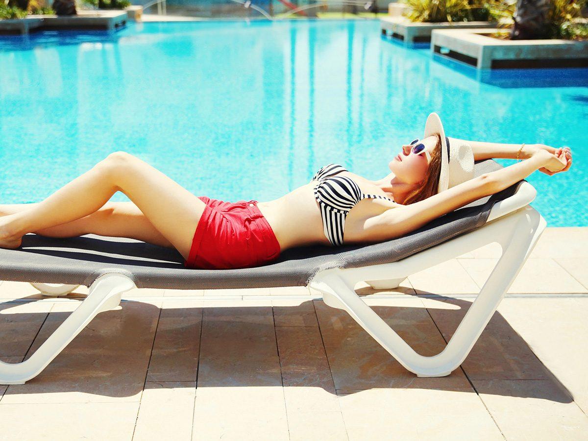 Aging, woman suntanning in bathing suit