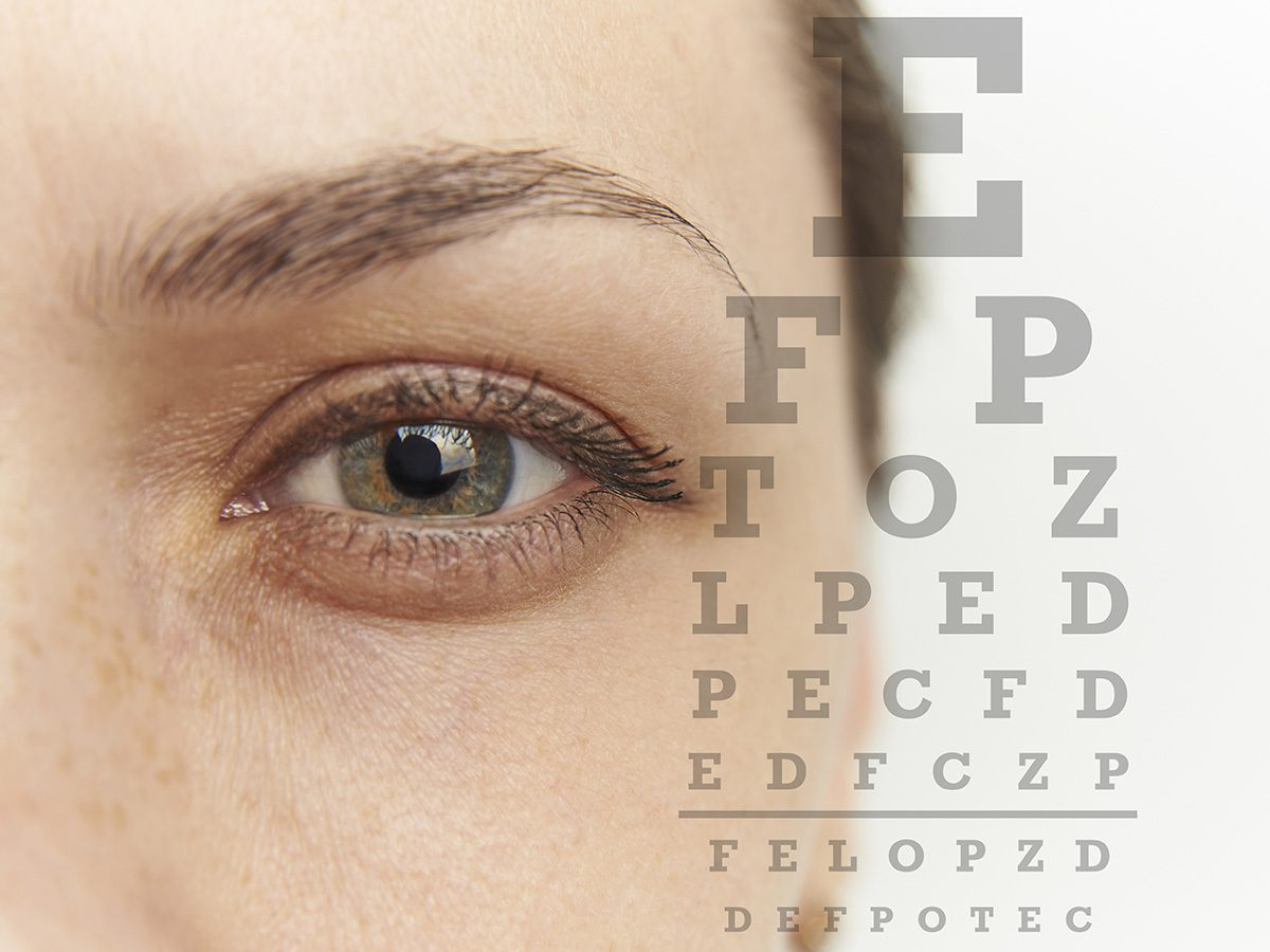 Blurry vision, Close-up of woman's eye as she squints to make out eye chart in the foreground