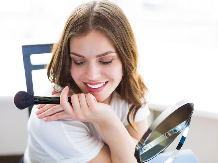 Burt's Bees, woman smiles in front of mirror as she applies blush
