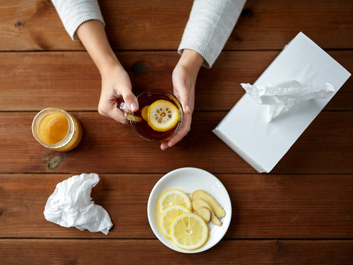 Cold weather, overhead shot of woman drinking lemon tea. Balled up tissues are on the table.