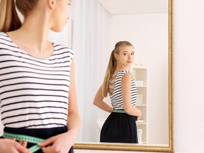 Cold weather, Young woman looks in mirror and measures her waist, She wears a striped T-shirt and black skirt.