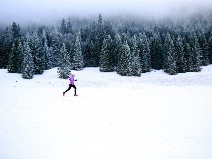 Cold weather, woman running in snowy field next to snow-covered fir trees.