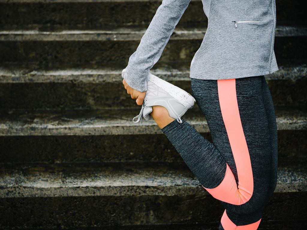 Cold weather, Woman stretching her quads in front of concrete steps. She wears running gear.
