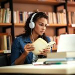 Cold weather, woman sitting at desk in library looking at laptop and listening on headphones. She also holds a notebook.