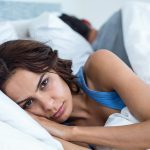 Conceive with PCOS, sad woman lies in bed wide awake while her husband sleeps