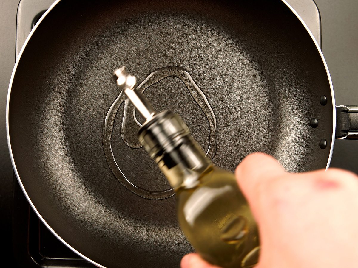 Cooking oil being drizzled into a frying pan