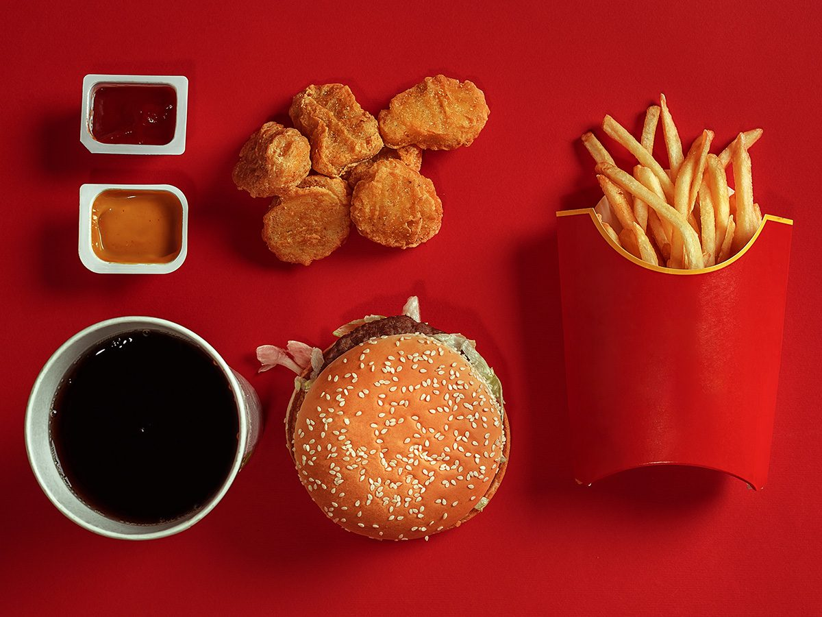 Fast food flatlay that includes chicken nuggets, coke, a burger and fries