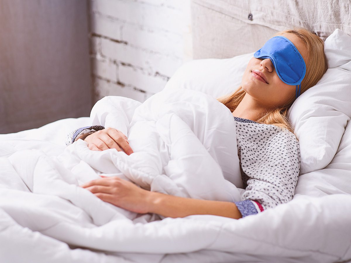 Flat stomach, woman happily sleeping in white bed with eye mask