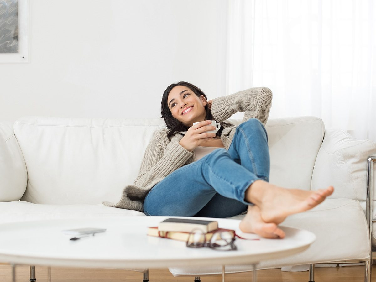 Green tea, woman relaxing on the couch with green tea in mug
