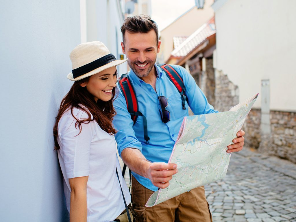 Happiness, couple looking at map in foreign destination