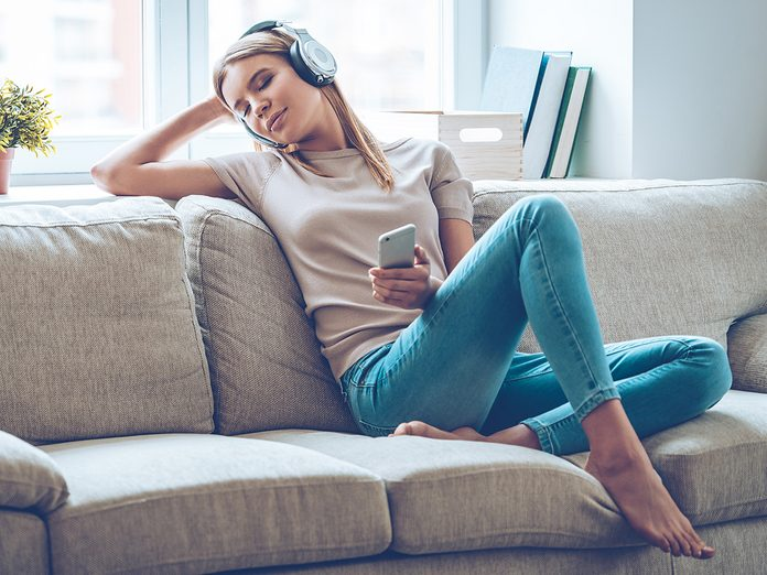 Happiness, woman sitting on couch listening to melancholy music with headphones