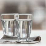 Health myth, two glasses of water side by side on a counter