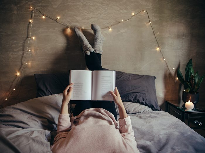 Health myth, a woman reads a book in her dimly lit bedroom