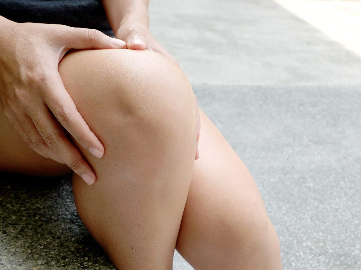 Health myth, a woman clutches her sore knee