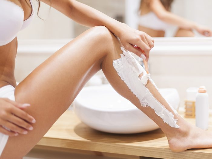 Health myth, woman in bra and underwear shaves her leg in the bathroom next to the sink