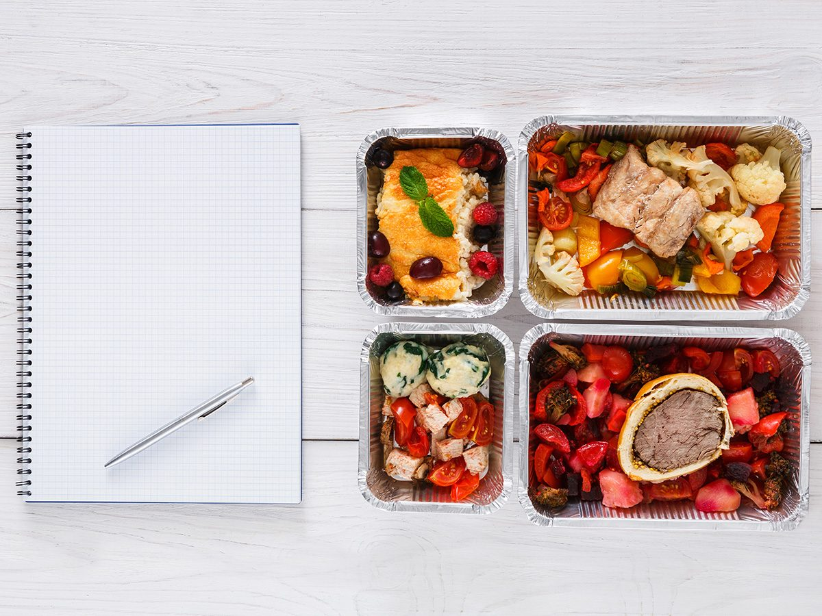 Healthy eating, An open notebook ready for meal planning and four meals in containers