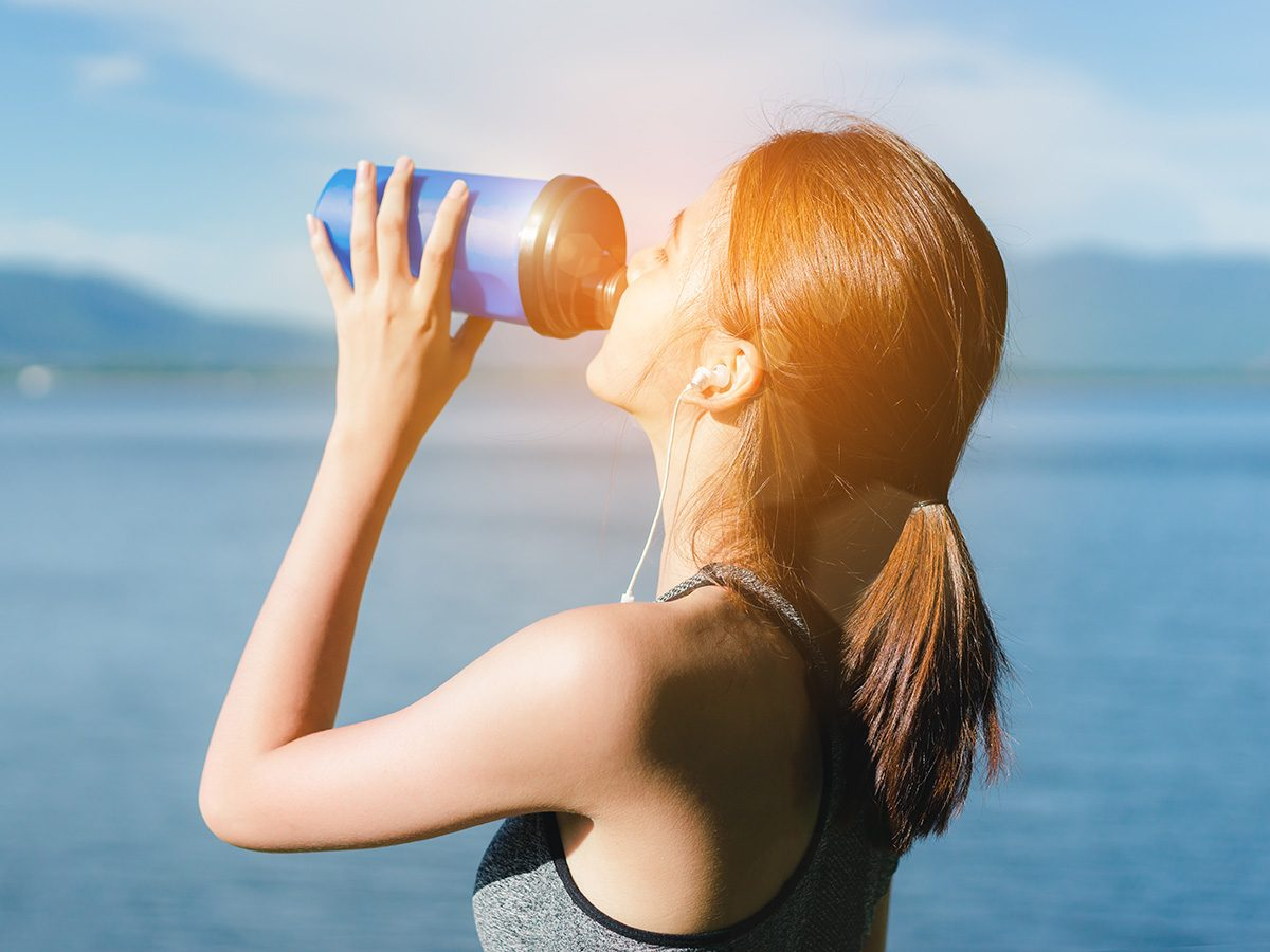 Healthy eating, Woman just finishes her workout and stands by a lake guzzling water from her water bottle.