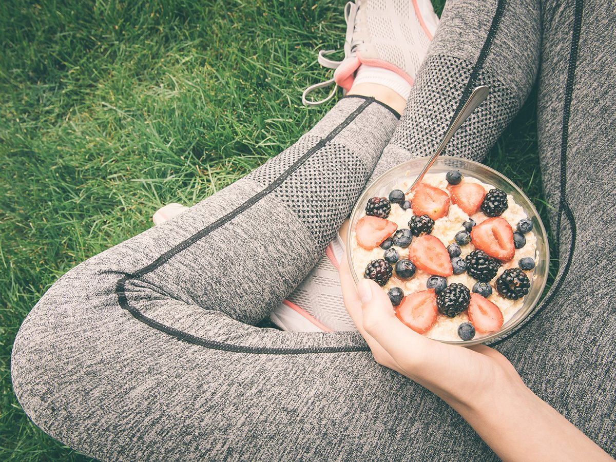 Healthy eating, Woman sits in workout clothes in grass and eats oatmeal and fruit