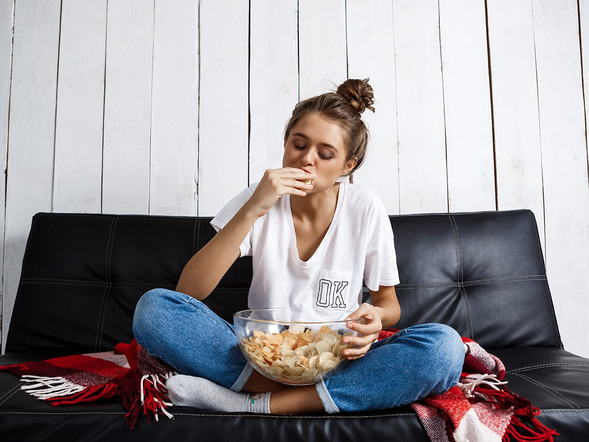 Healthy eating, woman sitting on the couch stuffing her face with chips