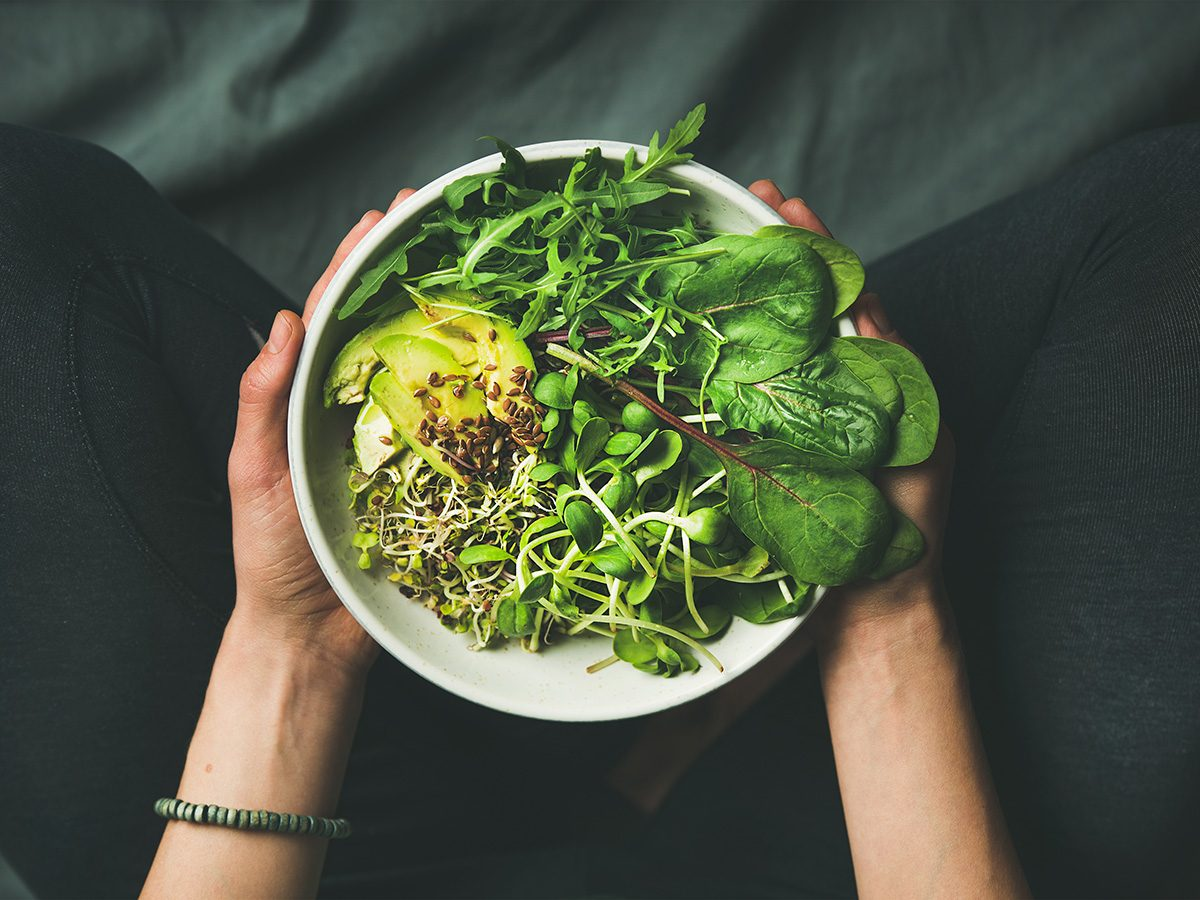 High cholesterol, Woman holding big bowl of salad in her lap