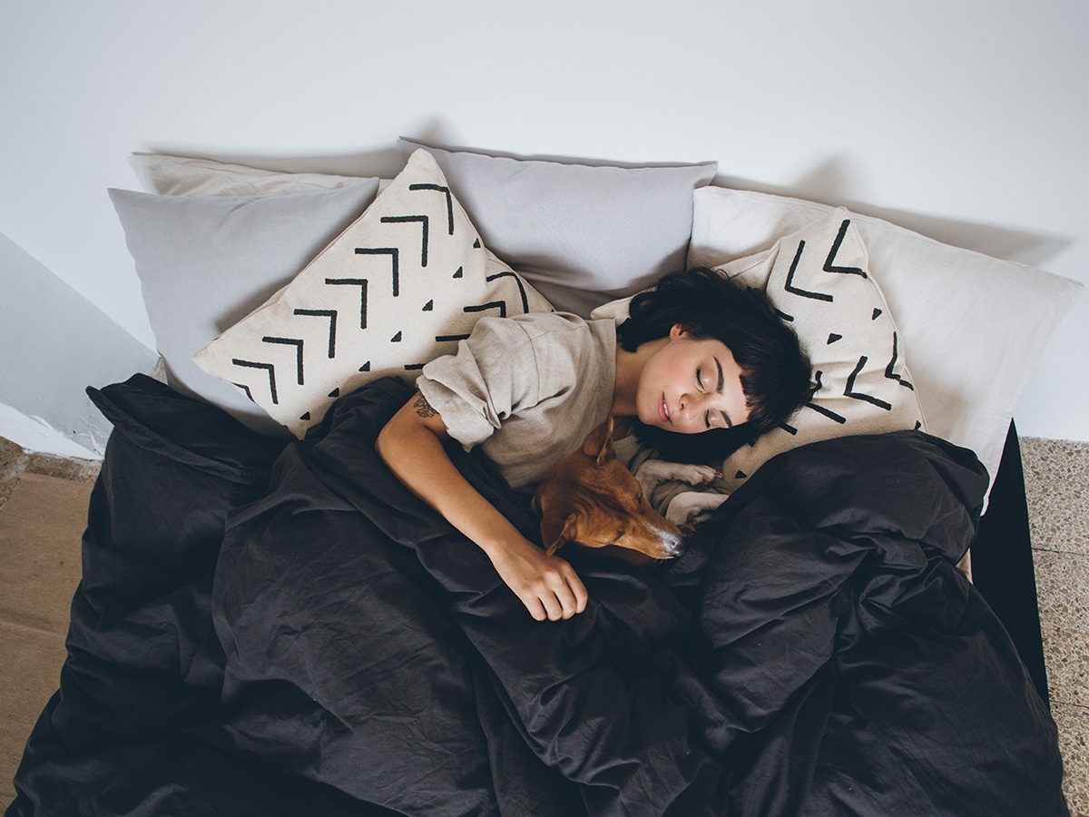 High cholesterol, Young woman lying in bed cuddling her dog
