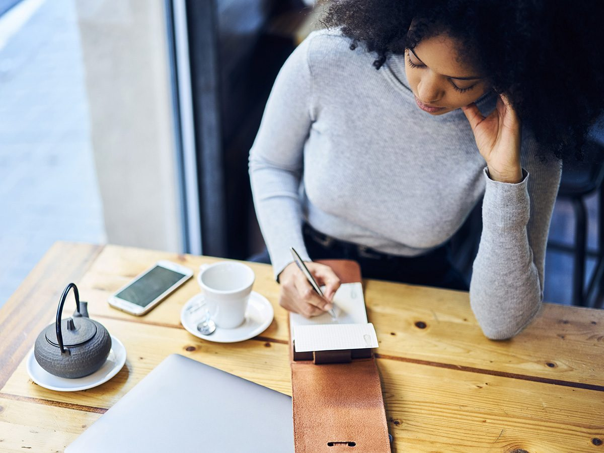 High cholesterol, woman drinking tea in coffee shop and going over to do list