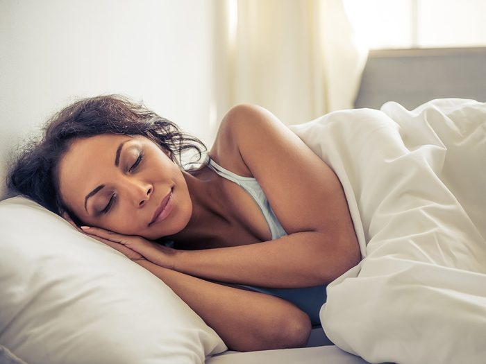 How to improve memory, Woman sleeping comfortably in all-white bed