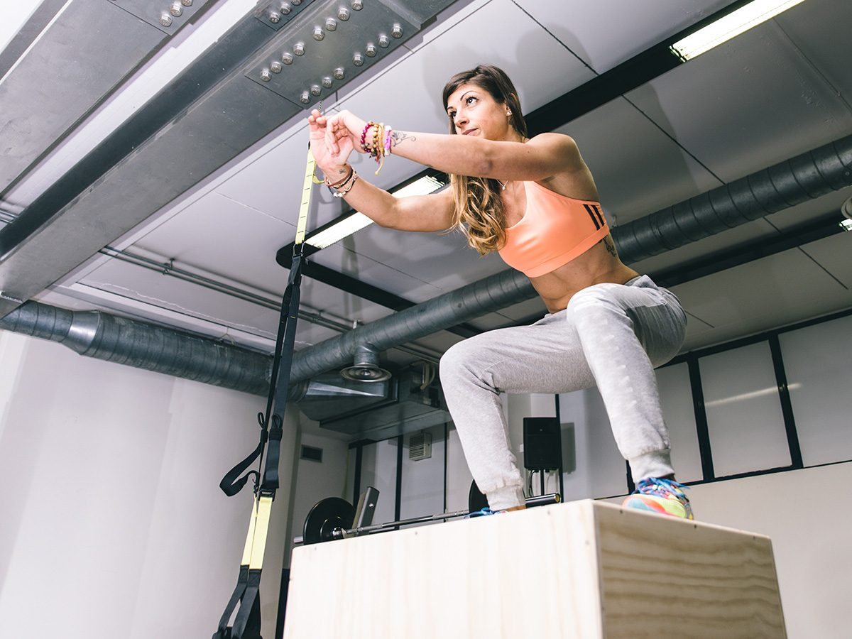 Jillian Michaels, woman at gym jumping on box