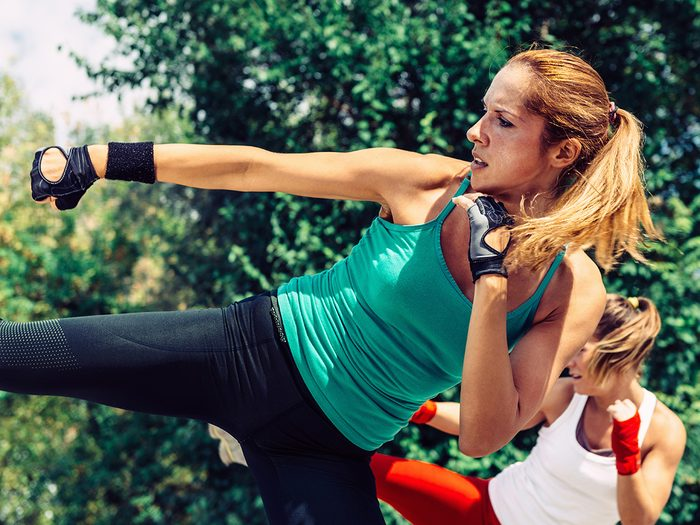 Jillian Michaels, woman outdoors doing a sidekick in a group