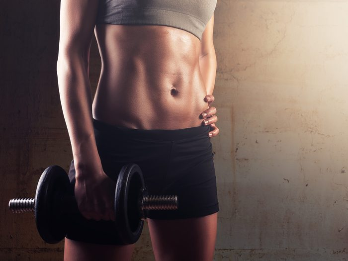 Fit woman holding a dumbell