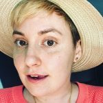 Lena Dunham smiling in hat. She just had a hysterectomy.
