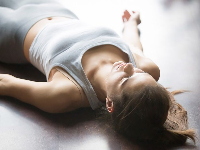 Meditation, woman in yoga clothes lying in ground relaxing and meditating with eyes closed