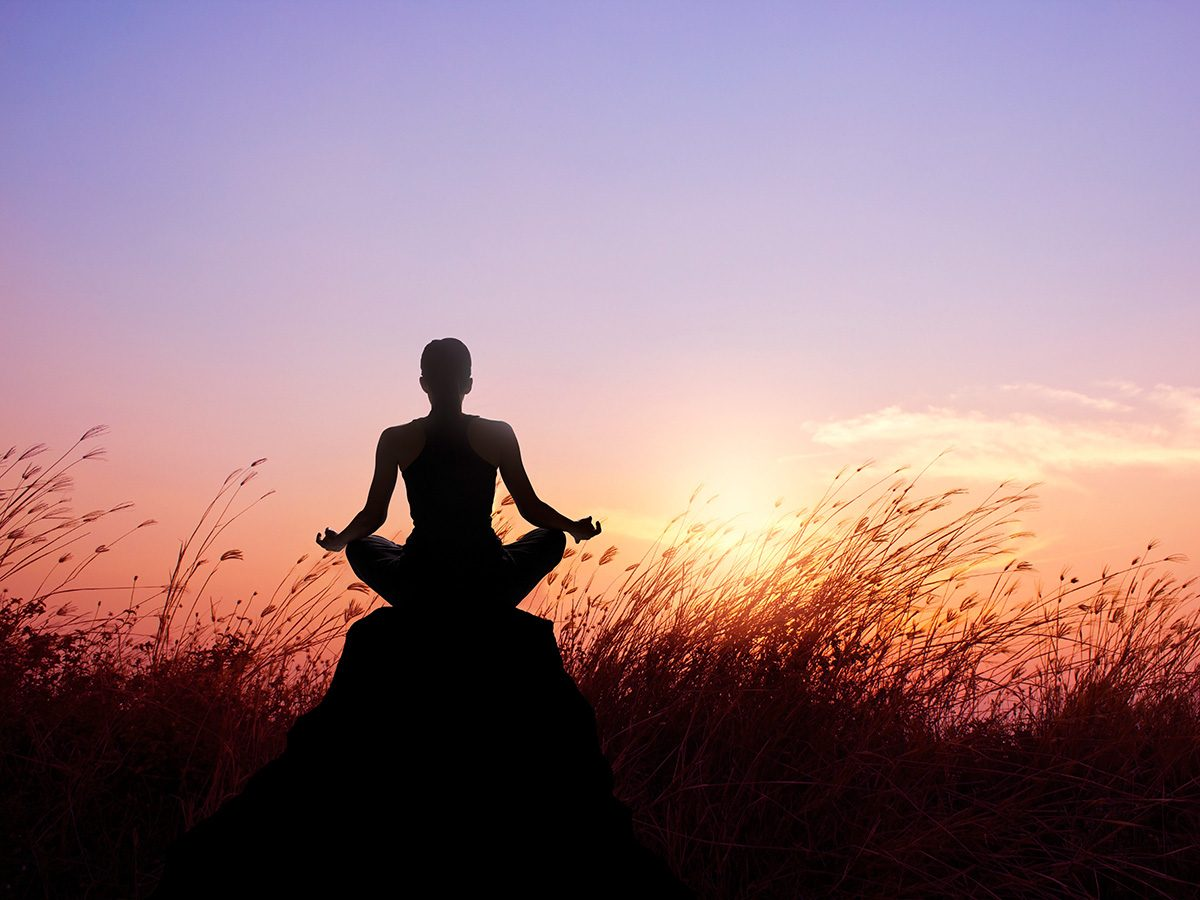 Meditation, Woman meditating at sunrise in a field