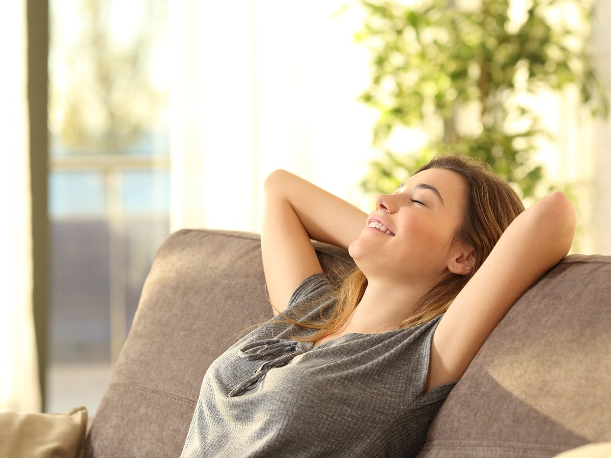 Meditation, Young woman stretching and sighing with her eyes closed as she sits on a couch in a sunny room