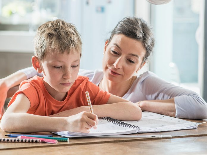 Memory test, mom helping son with his homework at the kitchen table
