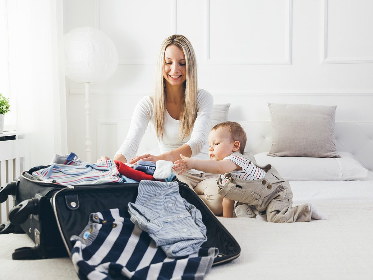 Memory test, Mom packing a suitcase on bed with toddler