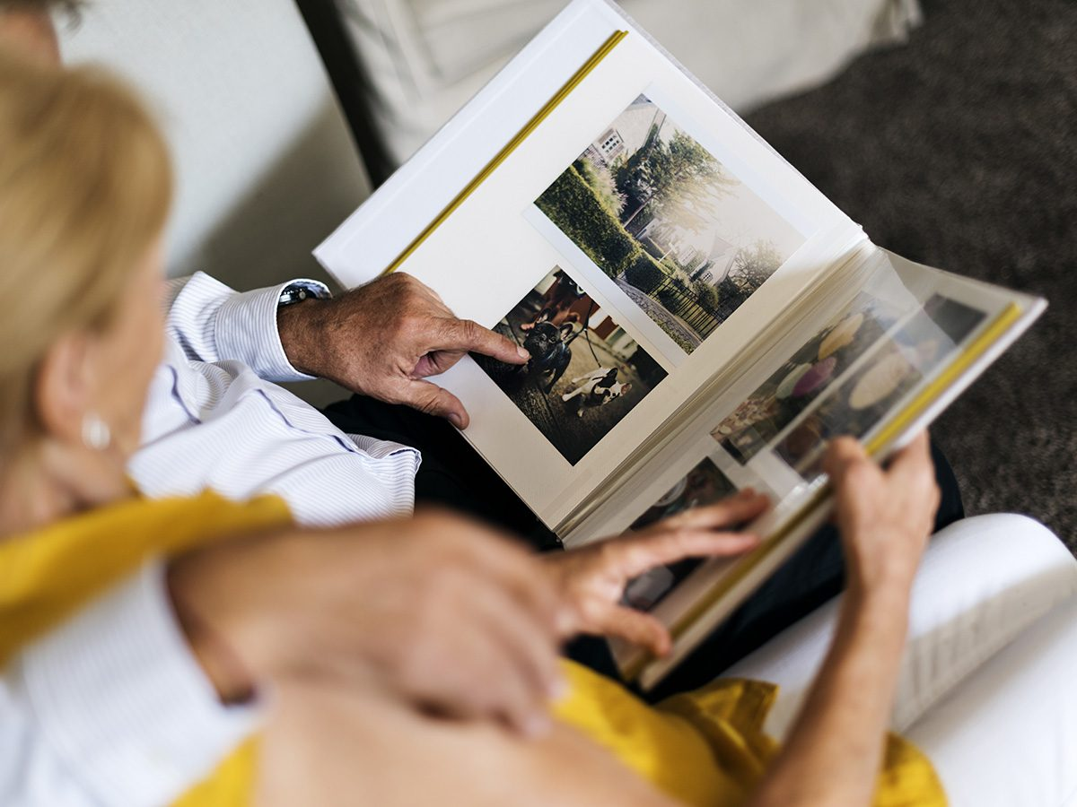 Memory test, elderly couple looking at photo album together while sitting on the couch