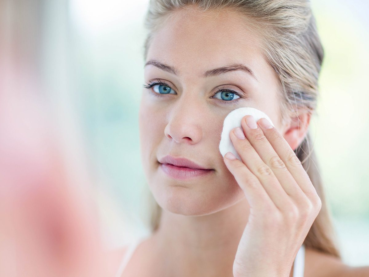 Woman uses micellar water to clean her face with a cotton pad