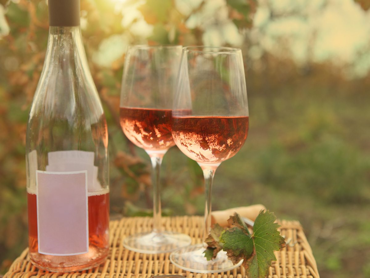 Pink wine bottle and glasses in vineyard
