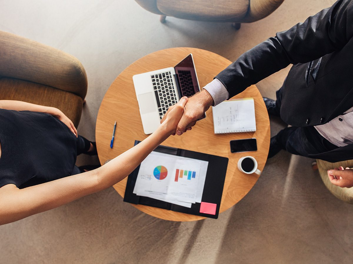 Productivity, man and woman shaking hands over a table with laptop and notes. Shot from above.