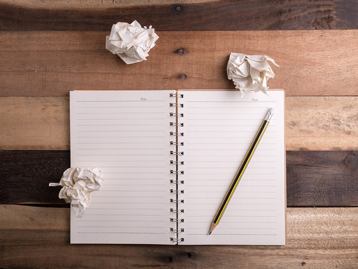 Productivity, blank open notebook with crumpled papers lying around it