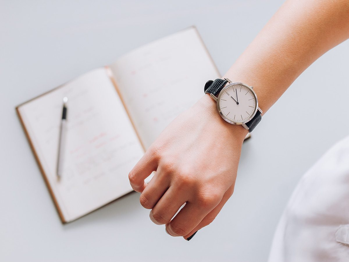 Productivity, close-up of woman's hand and watch above a notebook and pencil