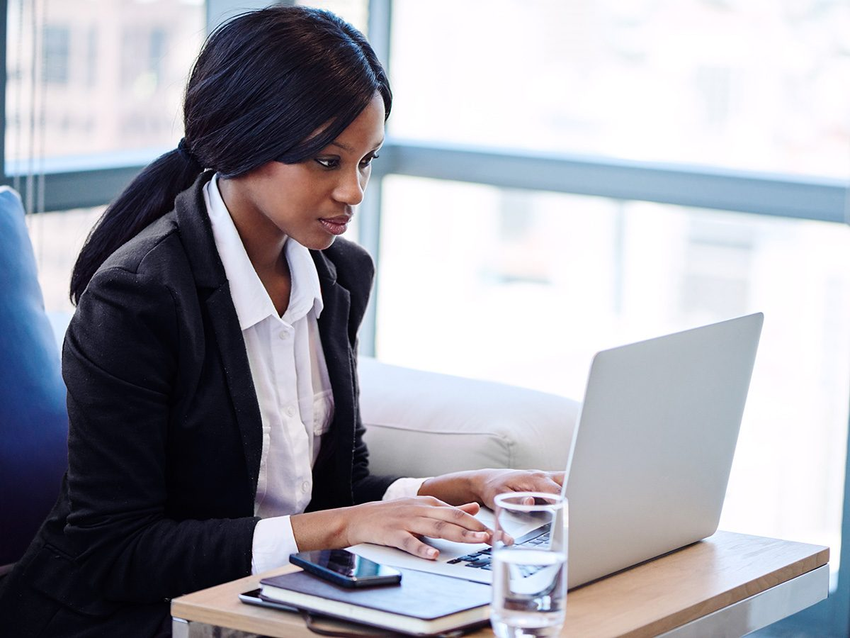 Productivity, Young woman in blazer focuses on her laptop screen, her hands on the keyboard