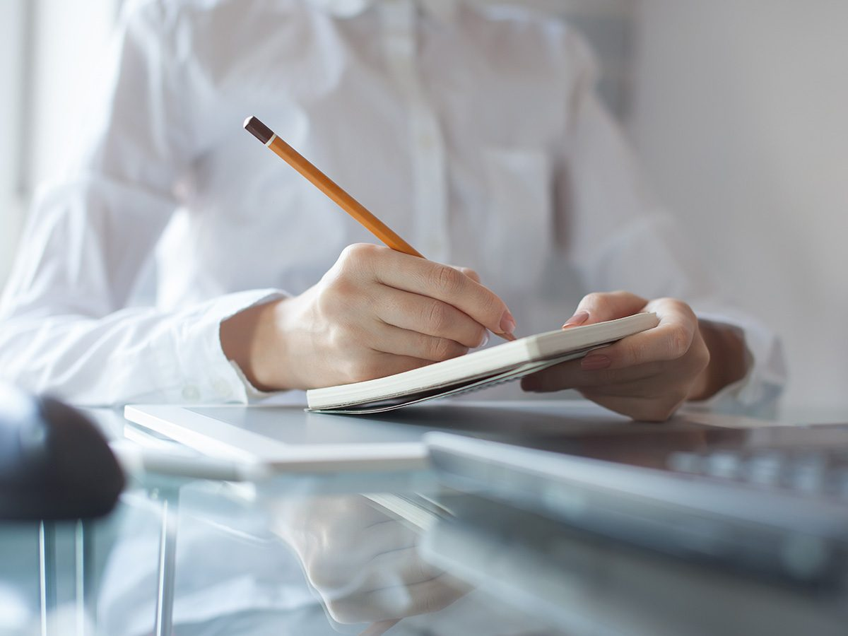 Productivity, woman in white shirt writing in notebook with pencil