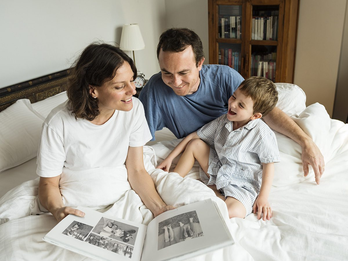 Rainy mood, family in bed looking at photo album