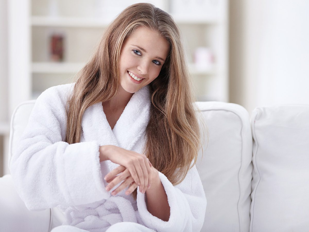 Rainy mood, woman in robe rubbing lotion on her hands